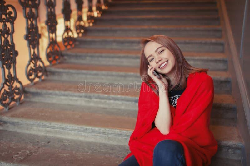 一个年轻白肤金发的女孩谈话在电话坐步,包裹在一条红色毯子 她是愉快和微笑 库存照片