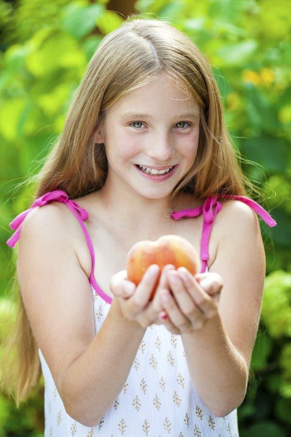 一个年轻白肤金发的小女孩的画象用桃子 免版税图库摄影