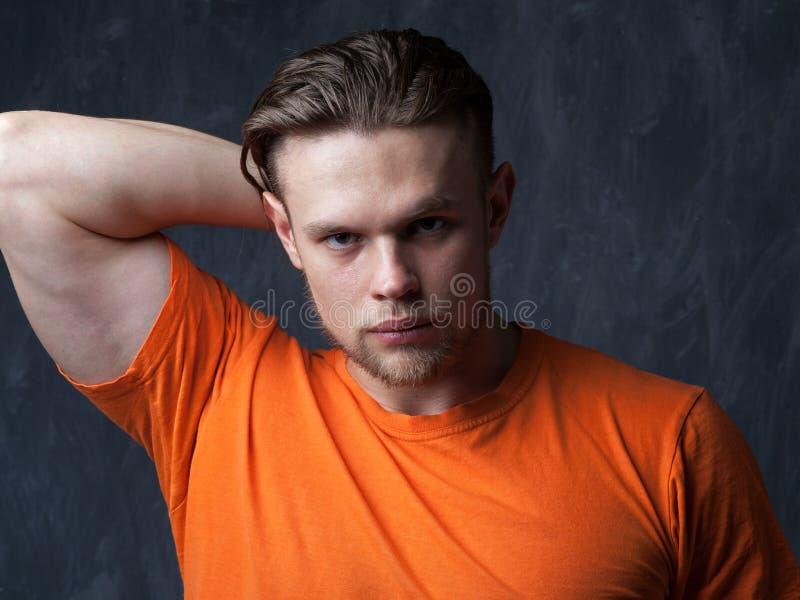 一个年轻肌肉人的画象橙色衬衣的 免版税库存照片