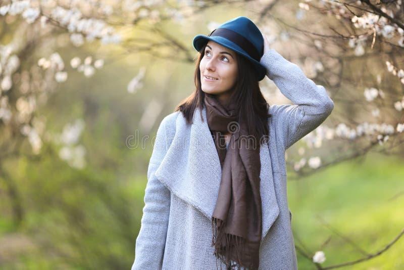 一个绿色帽子的女孩在一个开花的庭院里 免版税库存照片