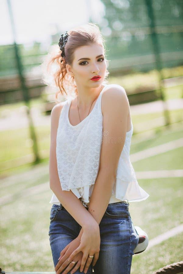 一个绿色橄榄球场的美丽的女孩 免版税库存照片
