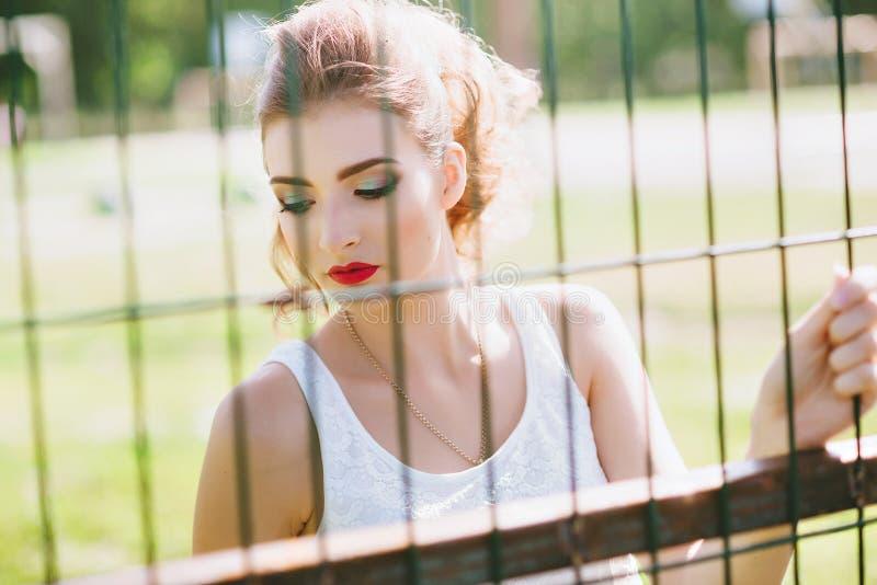 一个绿色橄榄球场的美丽的少妇 特写镜头画象 红色的嘴唇 免版税库存图片