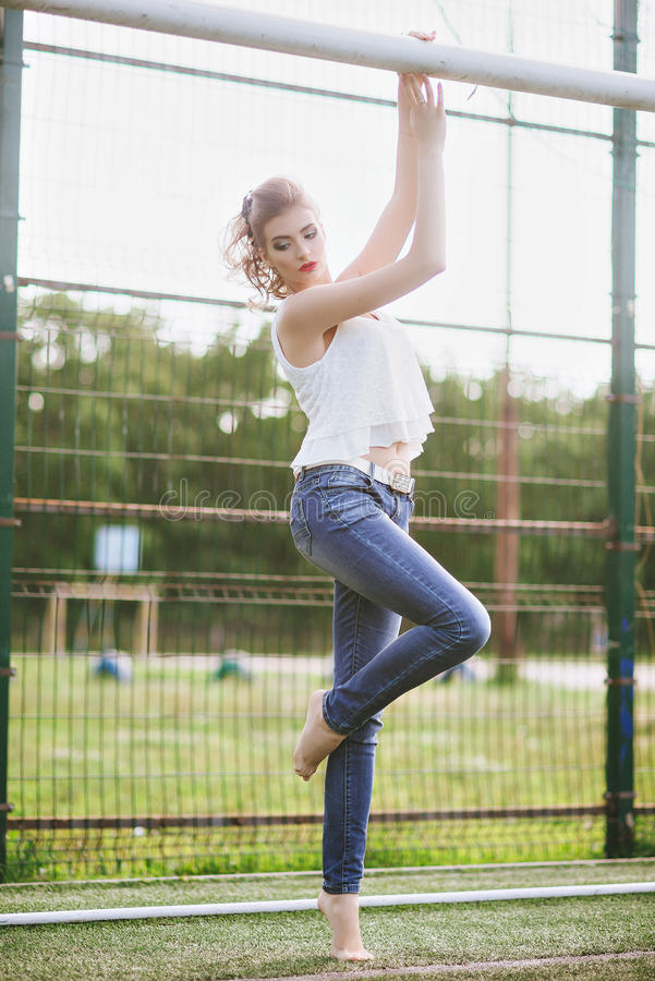 一个绿色橄榄球场的美丽的少妇 站立在橄榄球门的女孩,穿戴在蓝色牛仔裤,一件白色T恤杉 库存图片
