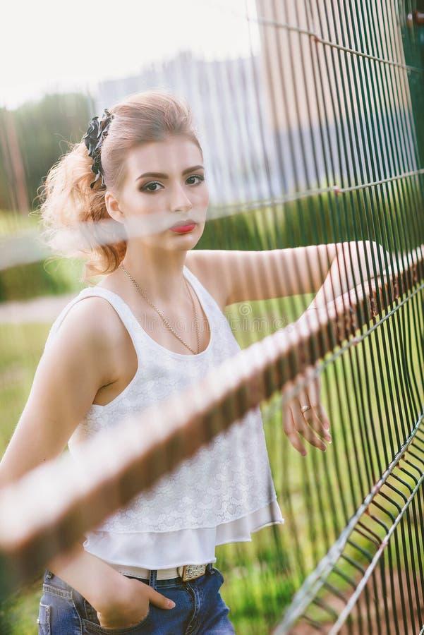 一个绿色橄榄球场的美丽的少妇 站立在橄榄球门的女孩,穿戴在蓝色牛仔裤,一件白色T恤杉 免版税库存图片