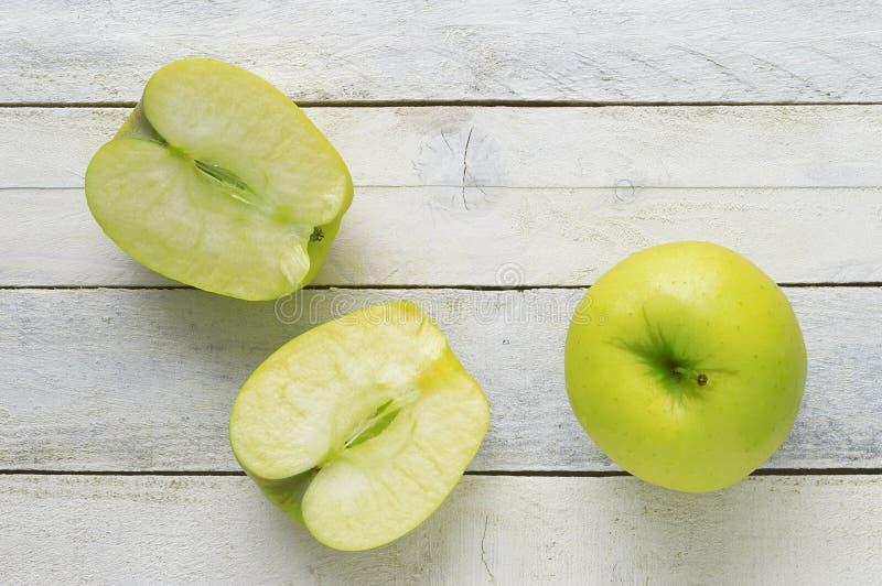一个绿色苹果和两个切片在一张白色木桌上 免版税库存照片