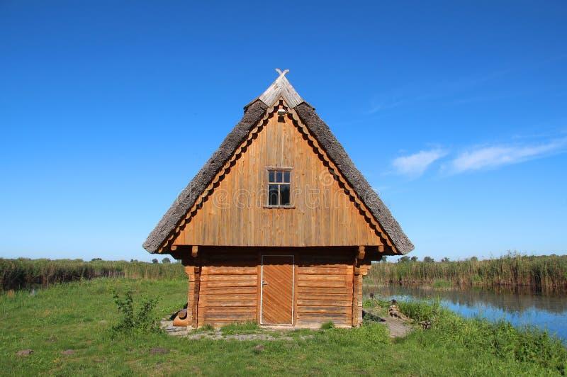 一个绿色领域的小木房子在湖旁边 免版税图库摄影