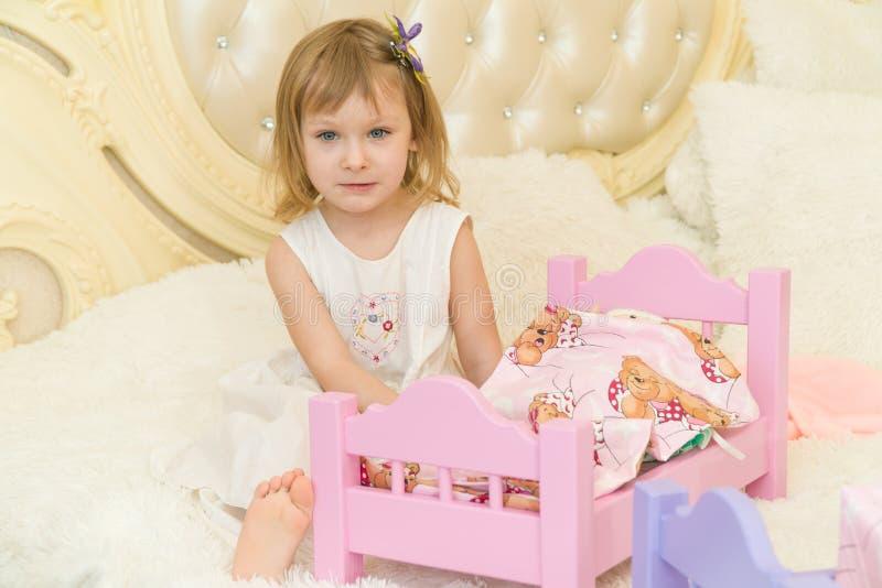一个活跃矮小的学龄前孩子,有白肤金发的卷发的一个相当小女孩,与她的玩偶的戏剧,投入他们睡觉 免版税图库摄影