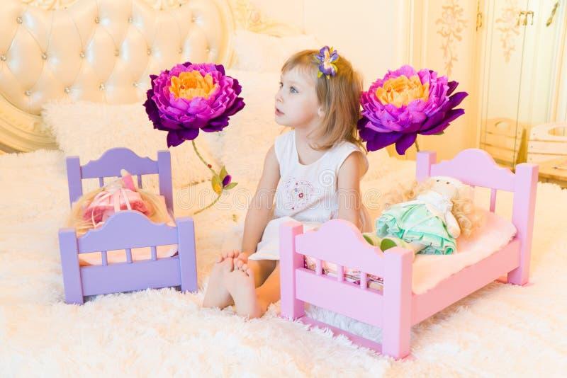 一个活跃矮小的学龄前孩子,有白肤金发的卷发的一个相当小女孩,与她的玩偶的戏剧,投入他们睡觉 库存图片