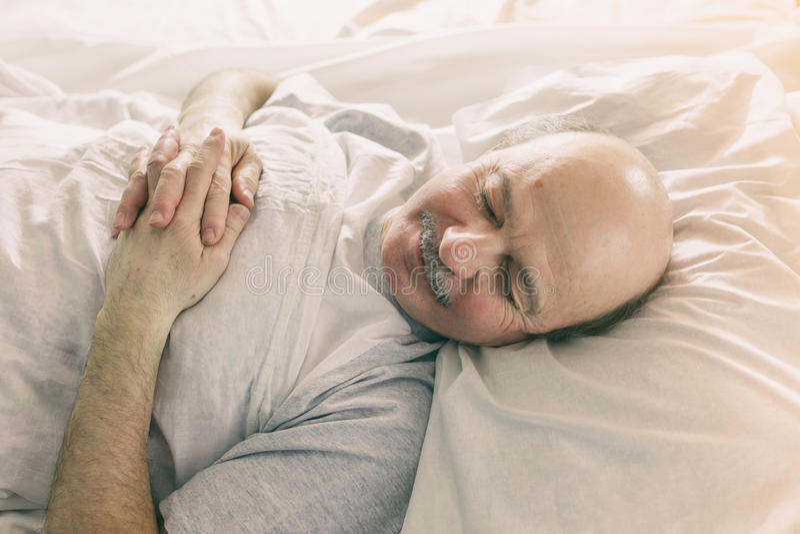 一个年长人在床上躺并且闭上他的眼睛 免版税图库摄影