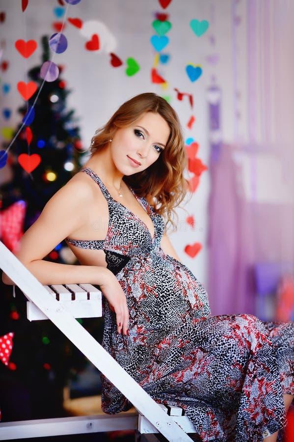一个年轻,美丽的女孩,未来母亲装饰了树和p 库存图片