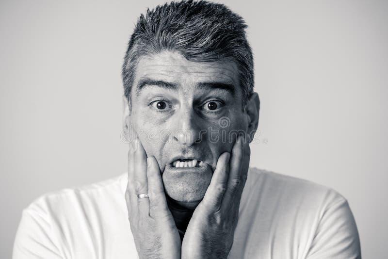 一个40s 50s人的画象震动的与在他的做在人的情感感觉的面孔的一个害怕的表示害怕姿态和 库存图片