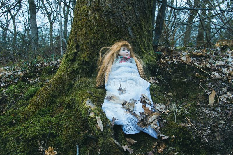 一个ceepy鬼的玩偶,坐在一个森林里在冬天 当黑暗,减弱的声音编辑 库存图片