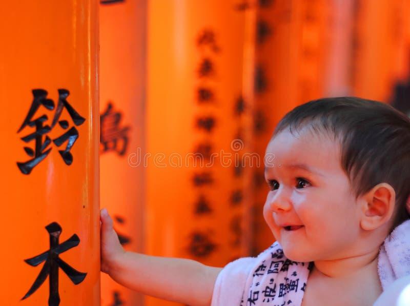 一个cherful矮小的婴孩的画象有Fushimi Inari Taisha寺庙红色五颜六色的toriis的在背景的 免版税库存图片