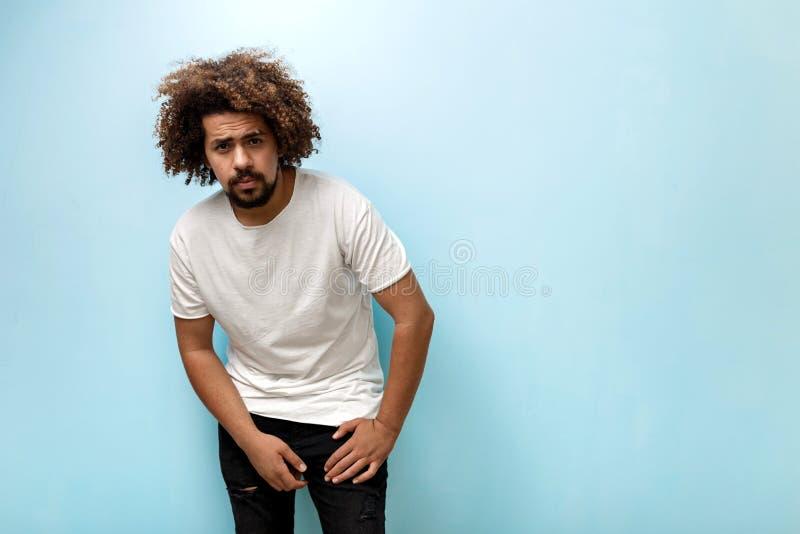 一个curly-headed深色的人倾斜今后佩带的白色T恤和被剥去的牛仔裤 人握在的手 库存照片