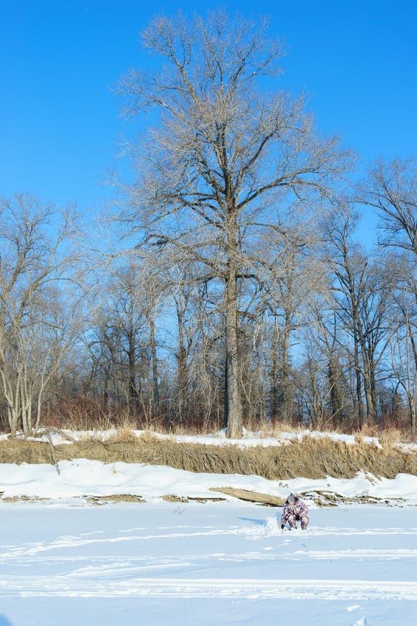 一个euriopean有胡子的人钓鱼接近孔冬天晴天在蓝天下 免版税库存图片