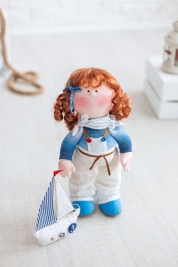 一个redhair水手玩偶和一艘船有一个风帆身分的在一个白色地板上 手工制造 库存照片