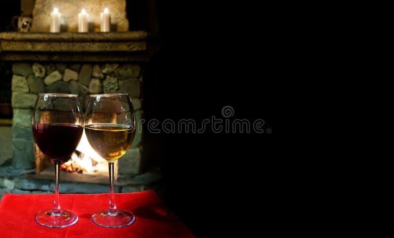 一个xmas晚上的舒适内部 两杯红色白葡萄酒,壁炉烟囱背景 浪漫xmas明信片 免版税图库摄影