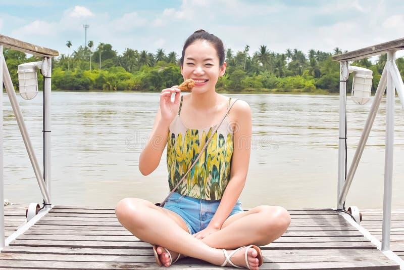 一亚裔美女采取在河旁边的休息 免版税图库摄影