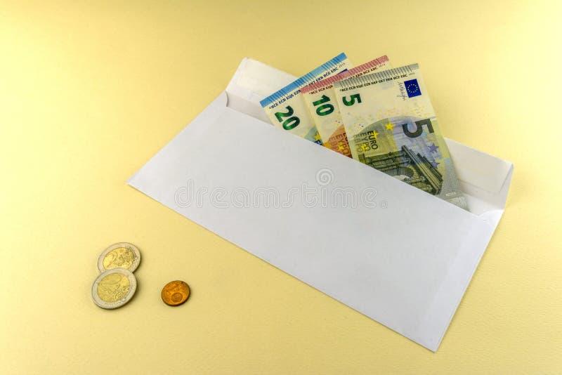 一些张欧元票据在信封 三枚欧元硬币在黄色背景说谎 库存图片