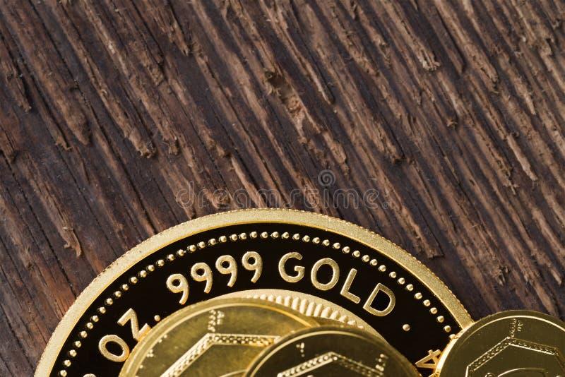 一些枚金币精致999 9在概略的木纹理背景  免版税库存照片