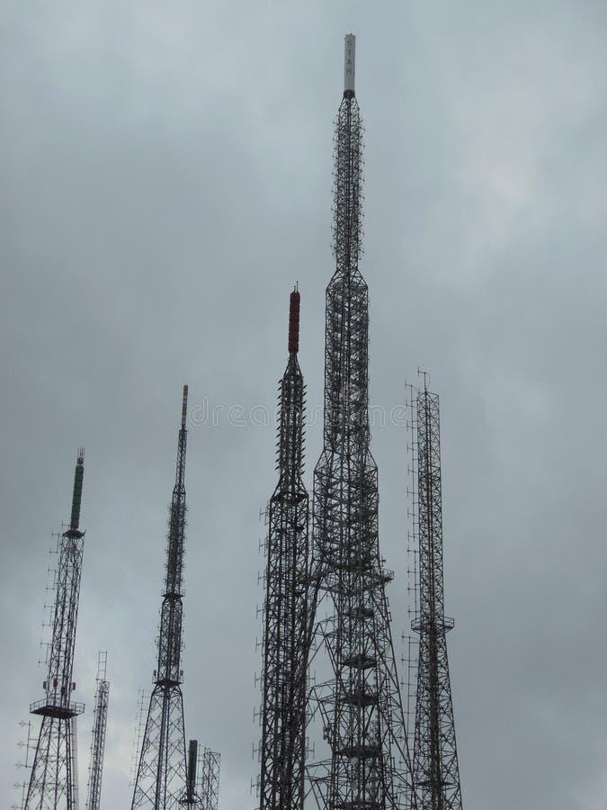 一些现出轮廓的天线,多云天空在背景中 免版税库存照片