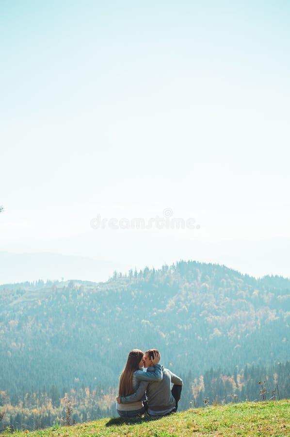 一些结合旅客男孩和女孩坐峭壁愉快情感生活方式概念年轻人家庭移动活跃 免版税库存照片