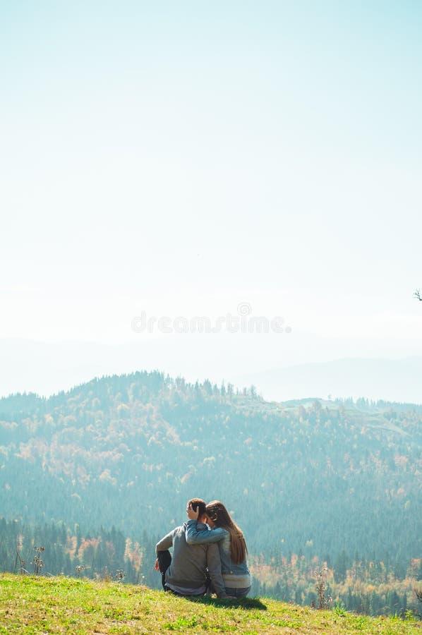 一些结合旅客男孩和女孩坐峭壁愉快情感生活方式概念年轻人家庭移动活跃 库存照片
