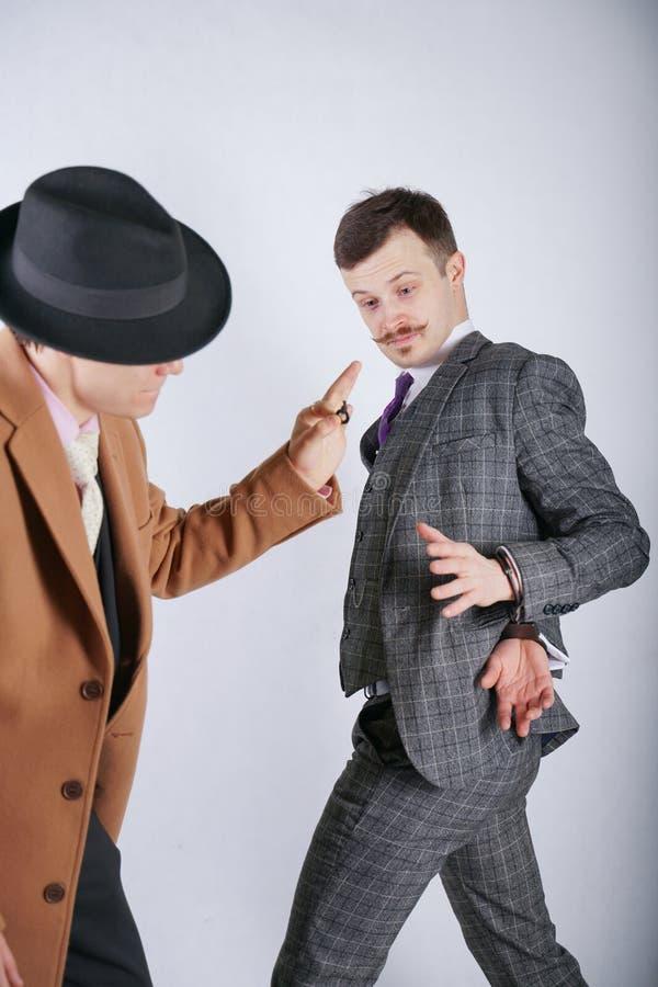 一人通过投入拘捕了别的在警察钢手铐和假装通过显示他钥匙并且珍惜自由 免版税图库摄影