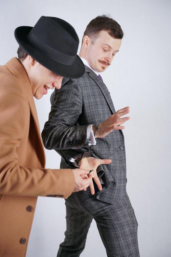 一人通过投入拘捕了别的在警察钢手铐和假装通过显示他钥匙并且珍惜自由 免版税库存照片