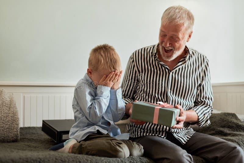 一代 祖父和孙子有礼物盒的在家坐长沙发 免版税库存照片