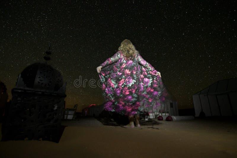 一件丝绸礼服的一名妇女看在营地的满天星斗的天空在尔格Chebbi沙漠中间 图库摄影