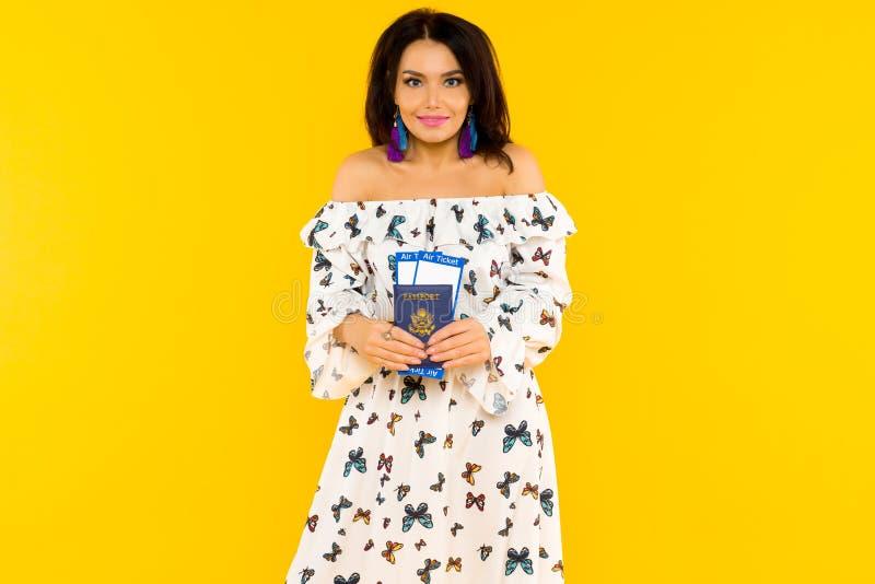 一件丝绸礼服的一名逗人喜爱的亚裔妇女有蝴蝶的有一本护照和机票在黄色背景 库存照片