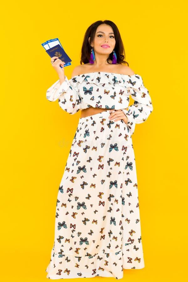 一件丝绸礼服的一名逗人喜爱的亚裔妇女有蝴蝶的有一本护照和机票在黄色背景 免版税库存照片