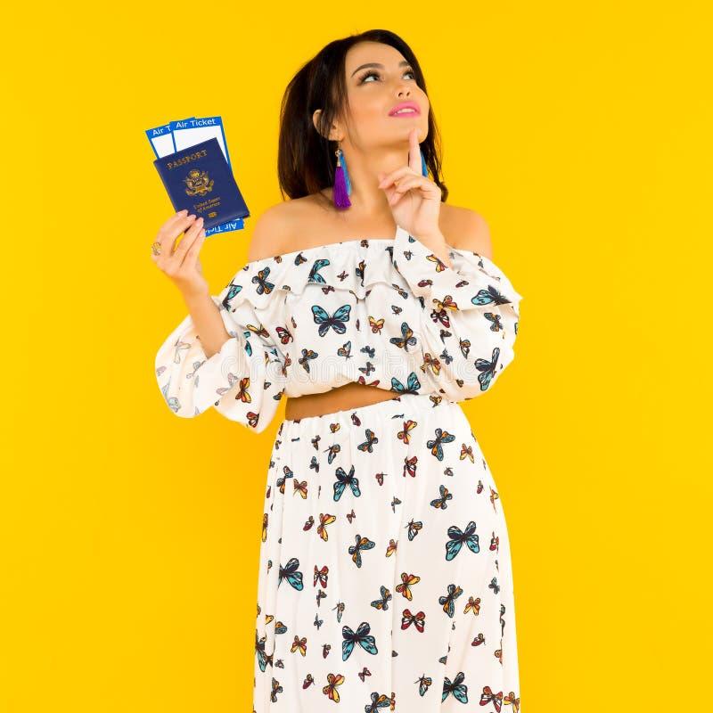 一件丝绸礼服的一名逗人喜爱的亚裔妇女有蝴蝶的有一本护照和机票在黄色背景 免版税库存图片