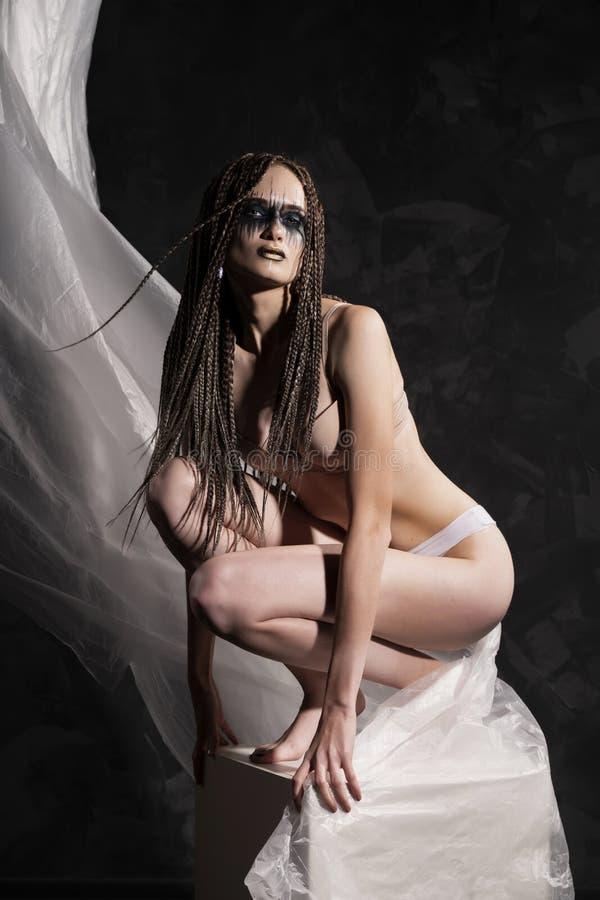 一件亭亭玉立的女孩佩带的内衣的剪影,坐反对玻璃纸影片背景  艺术性,创造性,概念性 免版税库存照片