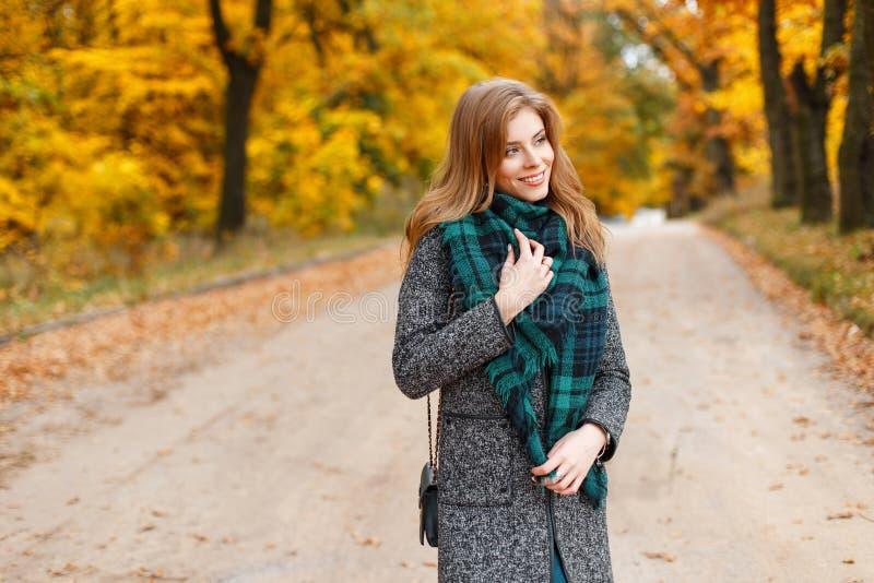 一件典雅的灰色外套的年轻俏丽的愉快的微笑的欧洲妇女有一条时兴的绿色温暖的围巾的在一个金黄公园走 免版税库存照片