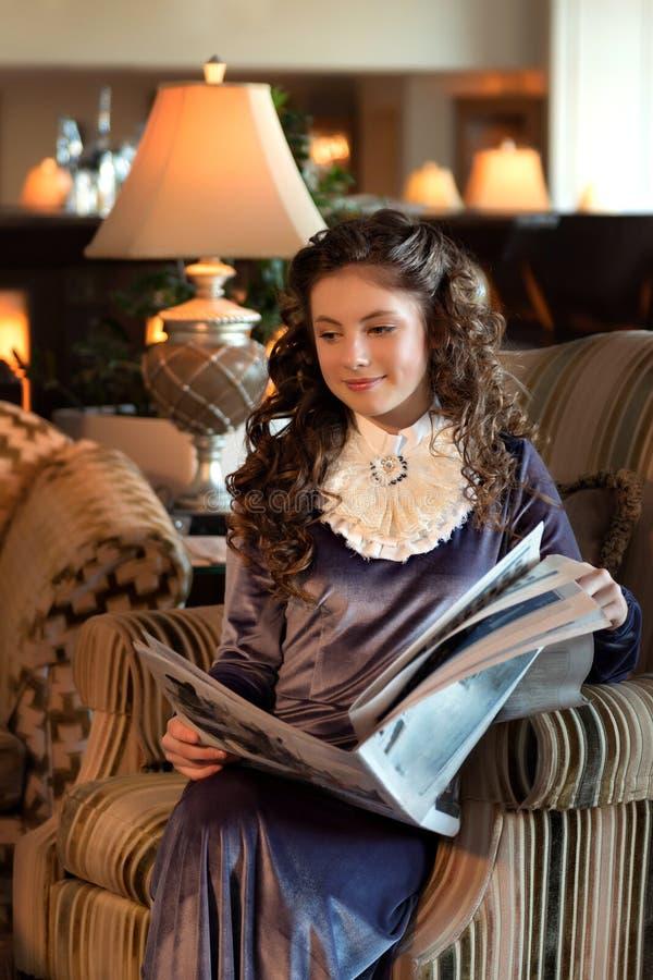 一件减速火箭的礼服的少女学生有胸部装饰的在一把古色古香的椅子坐并且读报纸沉思地作梦 免版税库存图片
