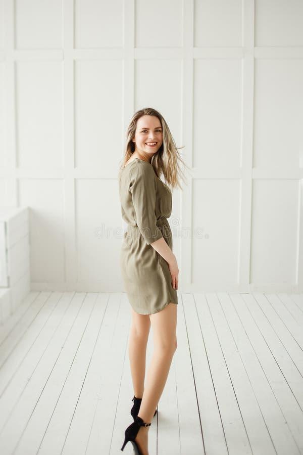 一件卡其色的礼服的美女在明亮的内部 吸引人妇女获得乐趣在短的礼服 愉快 免版税库存图片