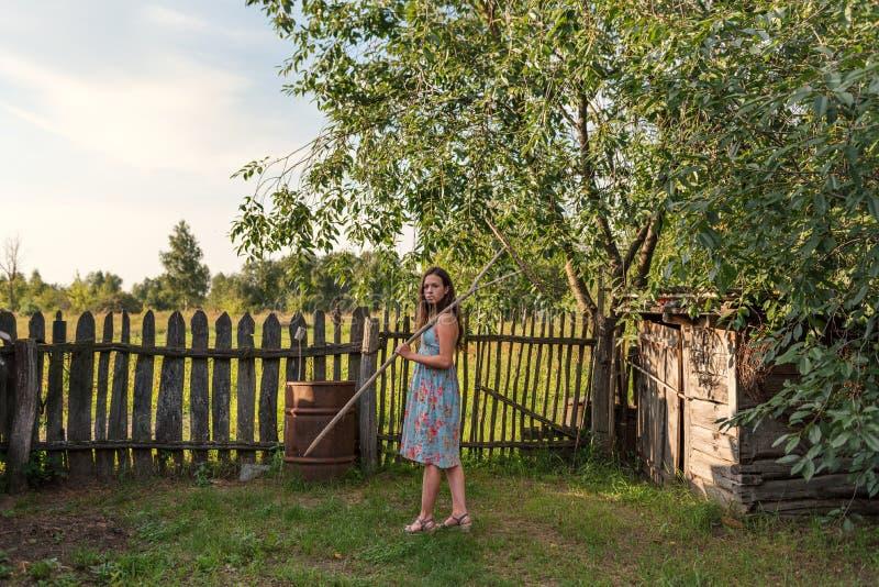 一件土气古板的礼服的一个女孩去拿着在一个农村庭院庭院的一把犁耙 免版税库存图片