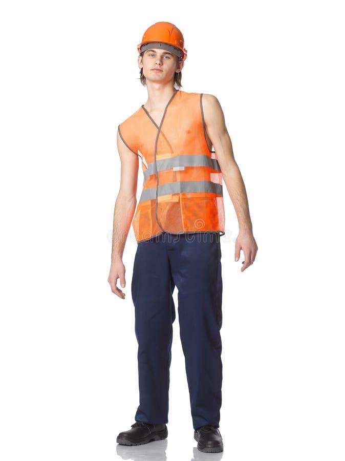 一件夏天橙色滤网背心的年轻工人在盔甲 库存图片