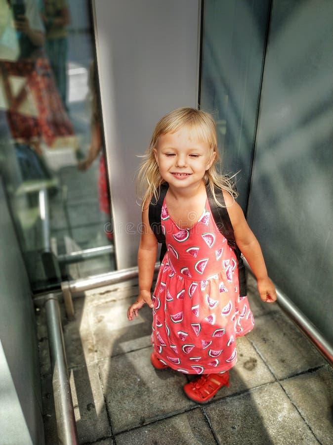 一件夏天浅粉红色的礼服的柔和的白肤金发的欧洲女孩在运动动力学在软的阳光下 免版税图库摄影