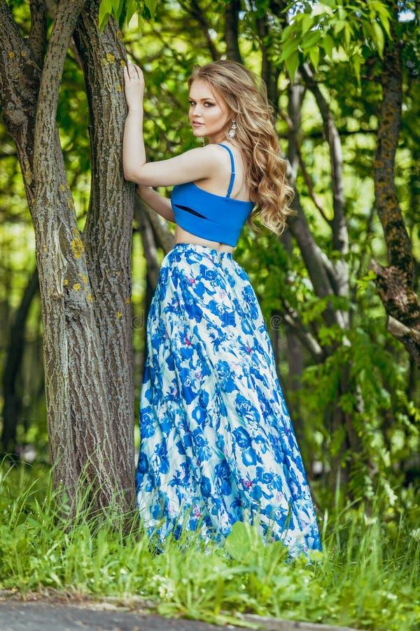 一件夏天礼服的美丽的少女在日落 在森林模型的时尚照片在一条蓝色上面和长的裙子,有流动的古芝的 免版税图库摄影