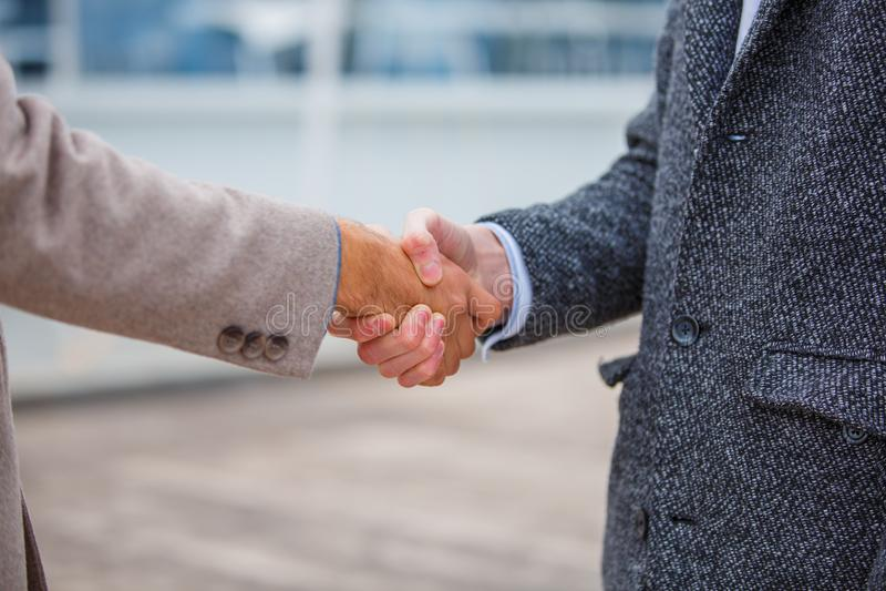 一件外套的商人在码头握手 免版税库存图片
