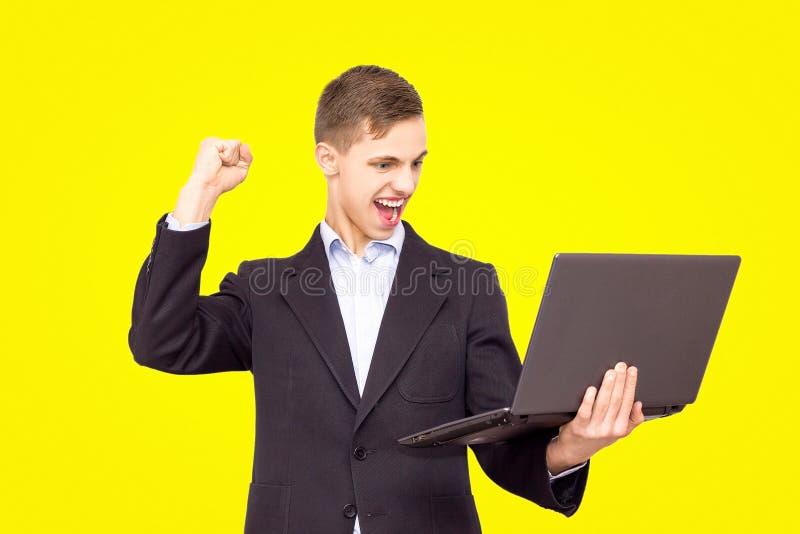 一件夹克和蓝色衬衣的人有膝上型计算机的在黄色背景高兴,隔绝 免版税图库摄影