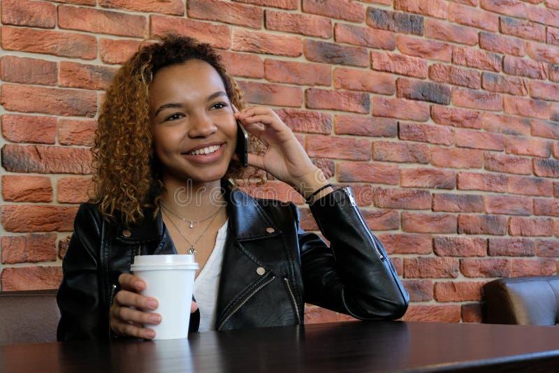 一件夹克的一名美丽的年轻非裔美国人的妇女有一块白皮书玻璃的在一只手上,坐在桌上和微笑,当ta时 免版税库存照片