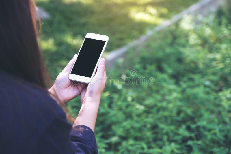 一件妇女藏品和使用有空白的黑桌面屏幕的白色巧妙的电话的大模型图象在室外与绿色自然 免版税库存照片