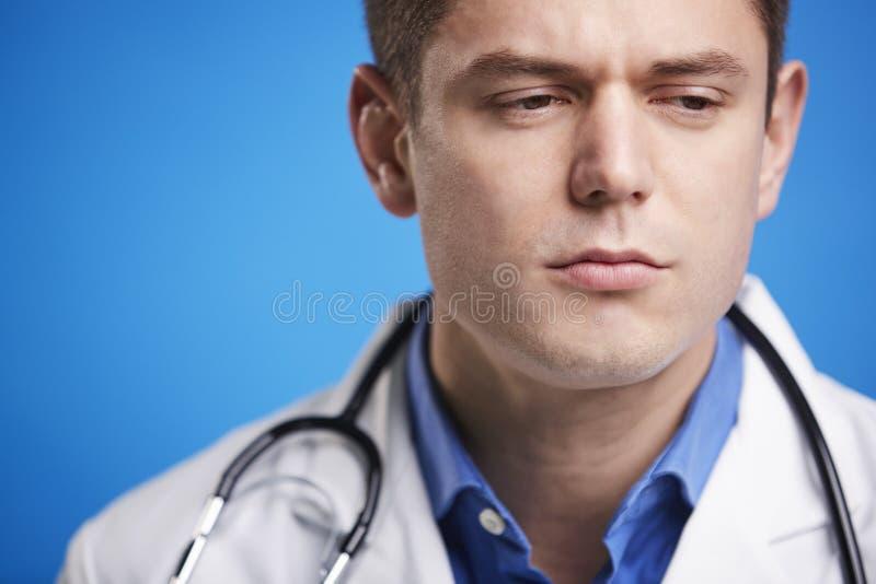 一件实验室外套的被注重的白男性医生有听诊器的 免版税图库摄影