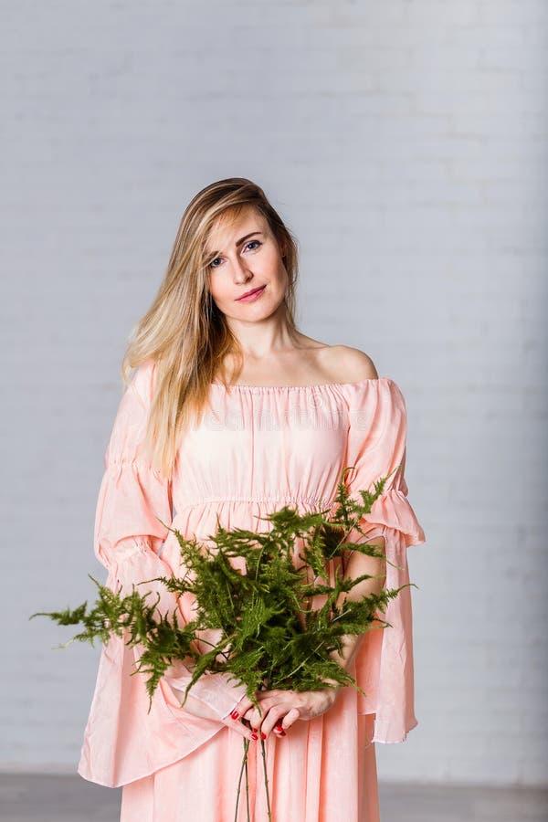 一件宽松桃子礼服的年轻白种人30岁的妇女在她的手上的拿着一个蕨分支 免版税库存照片