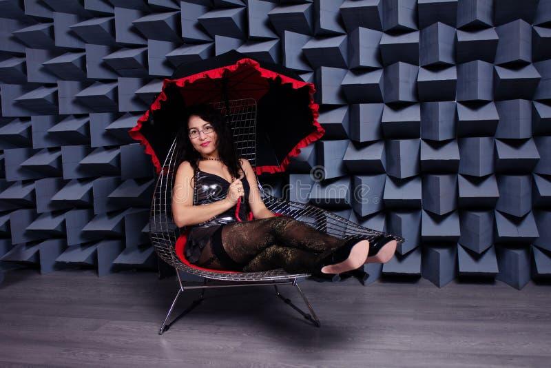 一件小黑礼服的美丽的性感的亚裔妇女在椅子, mo 库存图片