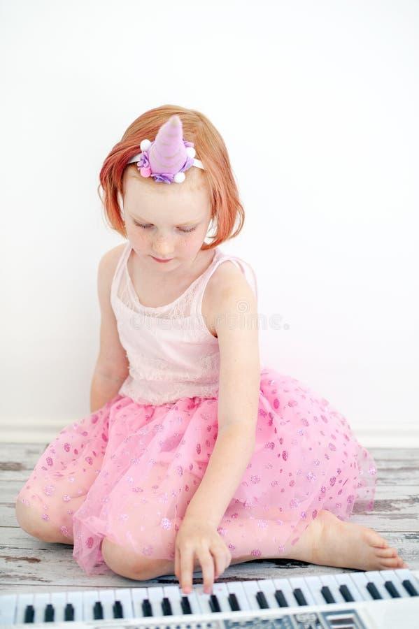 一件巧妙的礼服的一个女孩弹钢琴 免版税库存图片